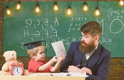 Teacher and pupil in mortarboard, chalkboard on background. Father teaches son elementary knowledge, discuss, explain. Elementary education concept. Kid stock photography