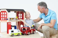 Teacher And Pupil Playing With Wooden Fire Station Stock Image