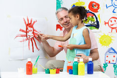 Teacher And Pupil In Pre School Art Class. Painting Stock Photo