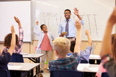 Teacher and pupil with raised hands at front of school class Royalty Free Stock Photos