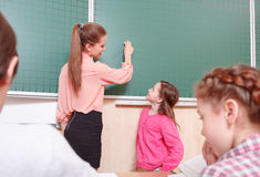 Teacher and pupil standing at blackboard. I will write. Smiling female teacher and pupil standing at blackboard, teacher is going to write on blackboard Stock Image