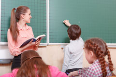 Teacher and pupil standing at blackboard. Ready to write. Young female smiling teacher and pupil standing at blackboard, pupil is going to write on blackboard Stock Photography