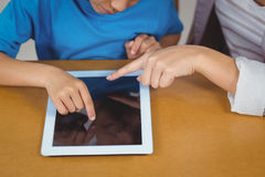 Teacher and pupil using tablet at his desk. In a classroom Royalty Free Stock Image