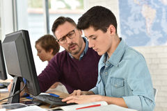 Teacher and pupils in computing class. Teacher in computing class assisting teenager with tablet Royalty Free Stock Photos