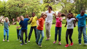 Teacher and pupils dancing together. Outside the elementary school stock footage