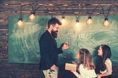 Teacher and pupils have lesson in class. Teacher write with chalk on chalkboard. Little girls listen to bearded man at. Teacher and pupils have lesson in class royalty free stock photo