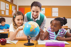 Teacher and pupils looking at globe Royalty Free Stock Image