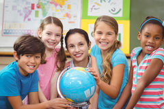 Teacher and pupils looking at globe Royalty Free Stock Photo