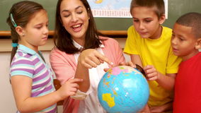 Teacher and pupils looking at globe. At the elementary school stock footage