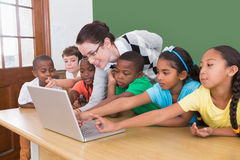 Teacher and pupils looking at laptop Royalty Free Stock Photos