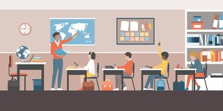 Teacher and pupils in the classroom. Teacher and pupils in a multicultural classroom, she is pointing to a world map and teaching geography Royalty Free Stock Images