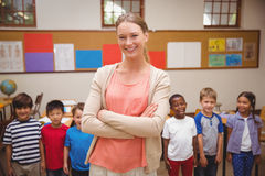 Teacher and pupils smiling at camera in classroom Stock Photography