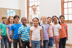 Teacher and pupils smiling at camera in classroom Stock Photos