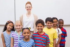 Teacher and pupils smiling at camera in classroom Royalty Free Stock Photography