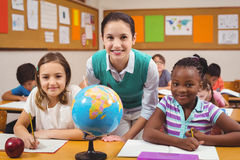 Teacher and pupils smiling at camera in classroom Stock Photo