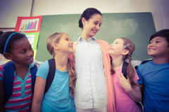 Teacher and pupils smiling in classroom Stock Images
