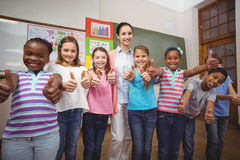 Teacher and pupils smiling in classroom Royalty Free Stock Photos