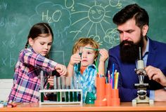 Teacher and pupils test tubes in classroom. Kids can grow in area of club such as science. Discover and explore. Properties of substances together. Chemistry royalty free stock photography