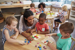 Teacher And Pupils Using Wooden Shapes In Montessori School Royalty Free Stock Image