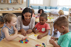 Teacher And Pupils Using Wooden Shapes In Montessori School Royalty Free Stock Images