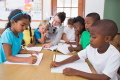Teacher and pupils working at desk together Royalty Free Stock Photography