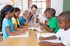 Teacher and pupils working at desk together Stock Photo