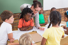 Teacher and pupils working at desk together Stock Photography
