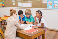 Teacher and pupils working at desk together Royalty Free Stock Photo