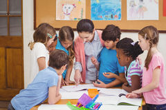 Teacher and pupils working at desk together Royalty Free Stock Photos