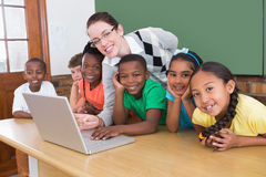Teacher and pupils working at laptop Stock Photo