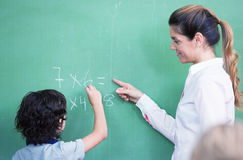 Teacher questioning kid at chalkboard Royalty Free Stock Image