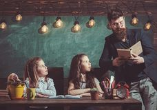 Teacher read book to pupils at lesson. Teacher teach schoolgirls in classroom. Bearded man and small girls in elementary. Teacher read book to pupils at lesson stock image