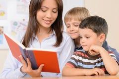 Teacher reading a book. Stock Photos