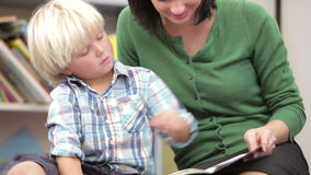 Teacher Reading Book With Male Pupil stock video