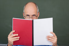 Teacher reading a book. Middle-aged balding male teacher reading a book which he is holding in front of his face so that only his eyes are visible Stock Photography