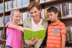 Teacher reading book with pupils at library Royalty Free Stock Image