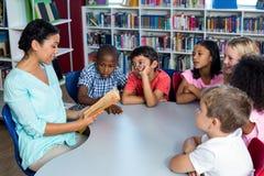 Teacher reading a book to children Stock Photo