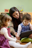 Teacher reading fairy tale to children at school stock image