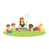 Teacher reading a fairytale to kids while sitiing on a carpet, childrens education and upbringing in school, preschool. Or kindergarten, colorful characters Stock Photography