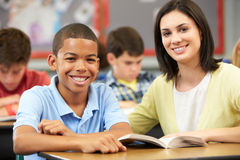 Teacher Reading With Male Pupil In Class Stock Photo