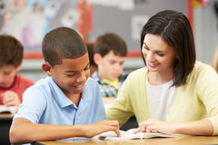 Teacher Reading With Male Pupil In Class Stock Image