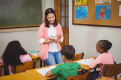 Teacher reading out loud to classroom Stock Image