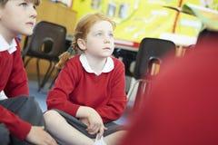 Teacher Reading Story To Elementary School Pupils Stock Photos