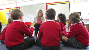 Teacher Reading Story To Elementary School Pupils. Pupils sit in circle on floor as teacher reads to them..Shot on Canon 5d Mk2 with a frame rate of 30fps stock footage