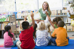 Teacher reading to children in library. Kindergarten teacher reading to children in library Royalty Free Stock Photos