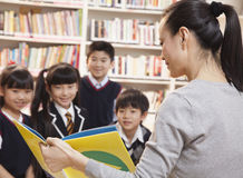 Teacher reading to her elementary school students Stock Images