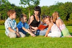 Teacher reading to kids stock photos