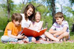 Teacher reads a book to children in a summer park Royalty Free Stock Photography