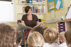 A teacher reads to a primary class