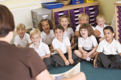 A teacher reads to schoolchildren in a class